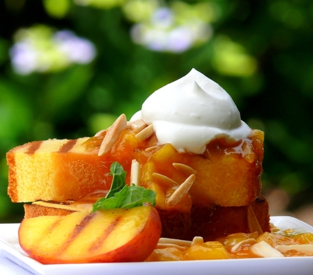 Carousel grilled pound cake with warm peach coulis and chantilly cream by noble pig