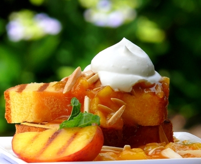 Medium grilled pound cake with warm peach coulis and chantilly cream by noble pig
